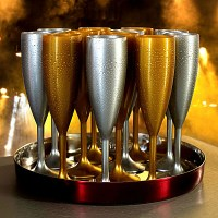 Silver & Gold Reusable Elite Plastic Champagne Flutes on a tray.